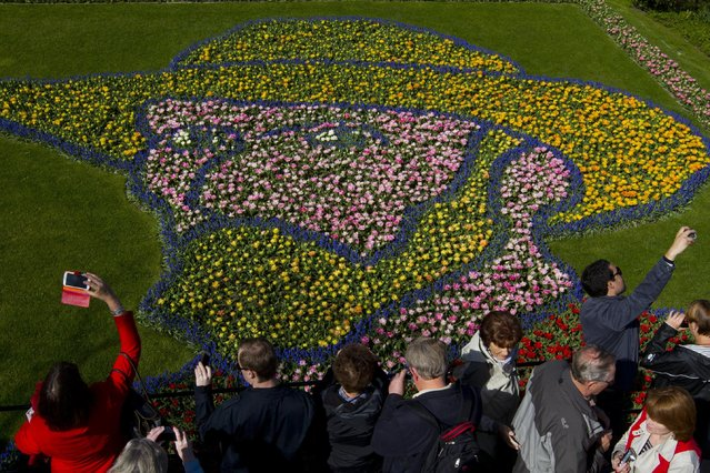 Tourists take pictures of a floral arrangement depicting Dutch master Vincent van Gogh at Keukenhof, a spring park with approximately seven million flower bulbs, in Lisse, Netherlands, Tuesday, April 21, 2015. (Photo by Peter Dejong/AP Photo)