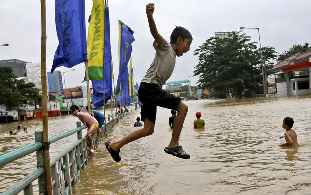 An Indonesian boy jumps into the water as he plays at a flooded part of the city in Jakarta, Indonesia, Wednesday, January 22, 2014. Seasonal rains and high tides in recent days have caused widespread flooding across much of Indonesia, an archipelago of more than 17,000 islands that's home to 240 million people. (Photo by Dita Alangkara/AP Photo)