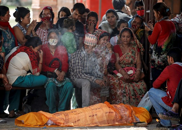 Relatives of a victim who died in Saturday's earthquake, mourn before the body is cremated along a river in Kathmandu, Nepal, April 27, 2015. (Photo by Danish Siddiqui/Reuters)
