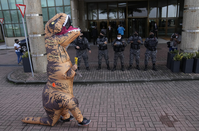 A protester in a dinosaur costume walks past police outside the Windsor hotel to show opposition to an auction taking place here for oil and gas exploration close to protected national marine park Fernando de Noronha, in Rio de Janeiro, Brazil, Thursday, October 7, 2021. Companies are competing for the exploration and production of oil and gas in the sedimentary basins of Campos, Santos, Potiguar and Pelotas. (Photo by Silvia Izquierdo/AP Photo)