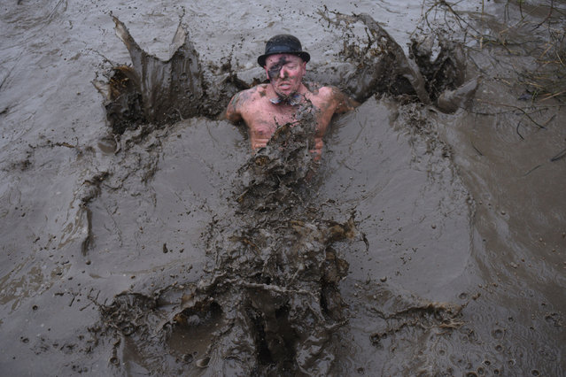 """A competitor goes into a muddy pool as he takes part in the """"Tough Guy"""" adventure race near Wolverhampton, central England, on January 29, 2017. (Photo by Oli Scarff/AFP Photo)"""