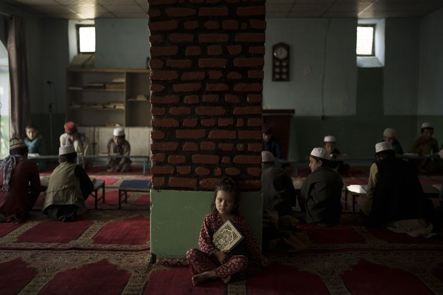 The niece of a teacher sits alone in a classroom as boys attend a class to memorize the Quran, Islam's holy book, at a madrasa in Kabul, Afghanistan, Tuesday, September 28, 2021. (Photo by Felipe Dana/AP Photo)
