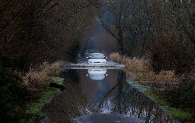 A car drives through flood water on the Somerset Levels on January 29, 2014 near Langport in Somerset, England. As weather forecasters predict more stormy weather, many villages on the Somerset Levels have faced weeks of flooding with the village Muchelney cut off because of flooded roads for almost a month. (Photo by Matt Cardy/Getty Images)