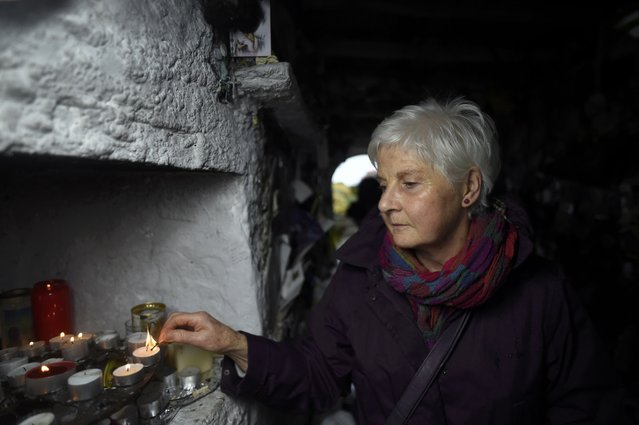A woman lights a candle at the holy well of St. Brigid on a Pattern Day pilgrimage to St. Brigid in Liscannor, Ireland February 1, 2017. (Photo by Clodagh Kilcoyne/Reuters)