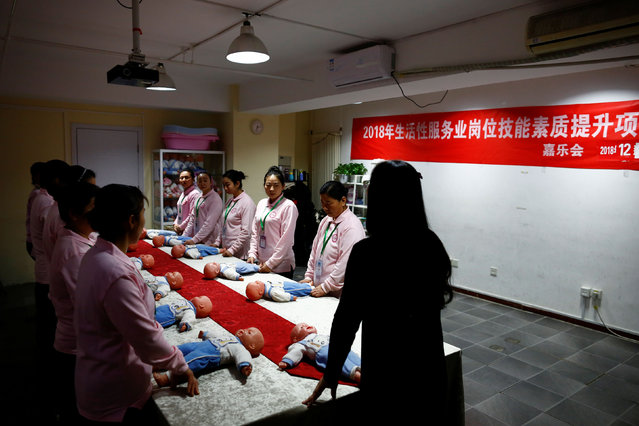 Students at Ayi University, a training program for domestic helpers, practice on baby dolls during a course teaching childcare in Beijing, China December 5, 2018. The training program teaches childcare, early education, housekeeping and other skills for domestic workers and is designed to meet the demand of China's middle class after the country scrapped the one-child policy. (Photo by Thomas Peter/Reuters)