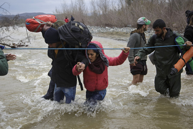 A woman is assisted while crossing the river along with other migrants, north of Idomeni, Greece, attempting to reach Macedonia on a route that would bypass the border fence, Monday, March 14, 2016. (Photo by Visar Kryeziu/AP Photo)