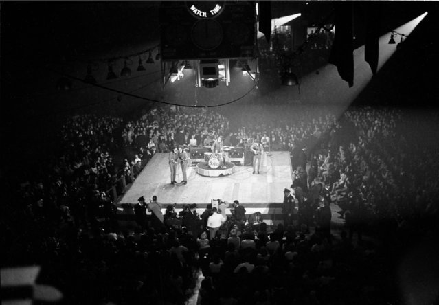 The Beatles perform at the Coliseum in Washington, D.C., February 12, 1964, during their first American tour.  The British band members are, in foreground, Paul McCartney and John Lennon; Ringo Starr on drums; and George Harrison on guitar, far right. (Photo by AP Photo)