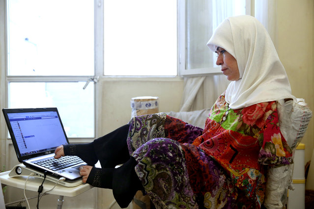 In this picture taken on Thursday, January 28, 2015, Zohreh Etezadossaltaneh works on her laptop at her home, in Tehran, Iran. (Photo by Ebrahim Noroozi/AP Photo)