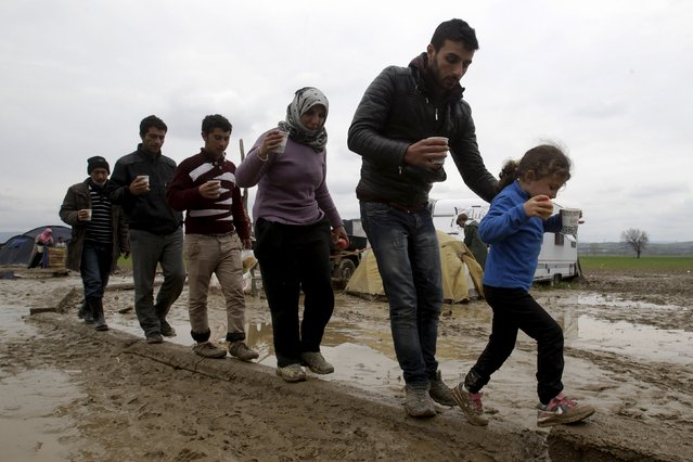 Refugees walk on a concrete bar to avoid stepping in the mud, at a makeshift camp for refugees and migrants at the Greek-Macedonian border, near the village of Idomeni, Greece March 16, 2016. (Photo by Alexandros Avramidis/Reuters)