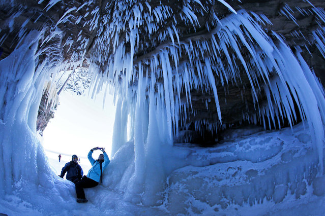 In this February 2, 2014 photo, people take pictures inside a cave at Apostle Islands National Lakeshore in northern Wisconsin, which has been transformed into a dazzling display of ice sculptures by the arctic siege gripping the Upper Midwest. (Photo by Brian Peterson/AP Photo/Minneapolis Star Tribune)