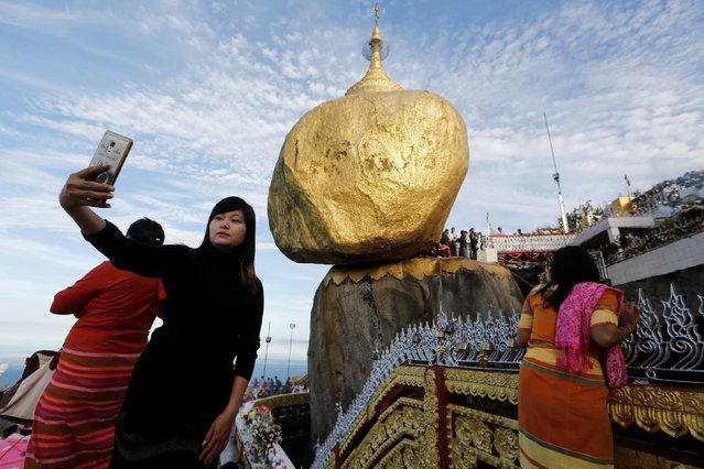 Buddhist pilgrims pray at Golden Rock, or Kyaikhtiyo Pagoda, in Kyaikto, Mon state, Myanmar October 25, 2018. (Photo by Ann Wang/Reuters)