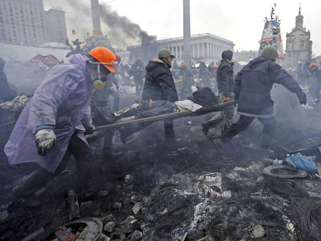 Anti-government protesters carry an injured man on a stretcher after clashes with riot police in the Independence Square in Kiev, on February 20, 2014. (Photo by Yannis Behrakis/Reuters)