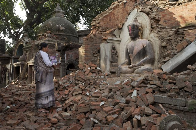 A Nepalese woman offers morning prayers at a temple damaged in last Saturday's earthquake in Bhaktapur, Nepal, Saturday, May 2, 2015. A week after the devastating earthquake, life is limping back to normal in Nepal with residents visiting temples on the first Saturday after the quake, a day normally reserved for temple visits. (Photo by Bernat Amangue/AP Photo)