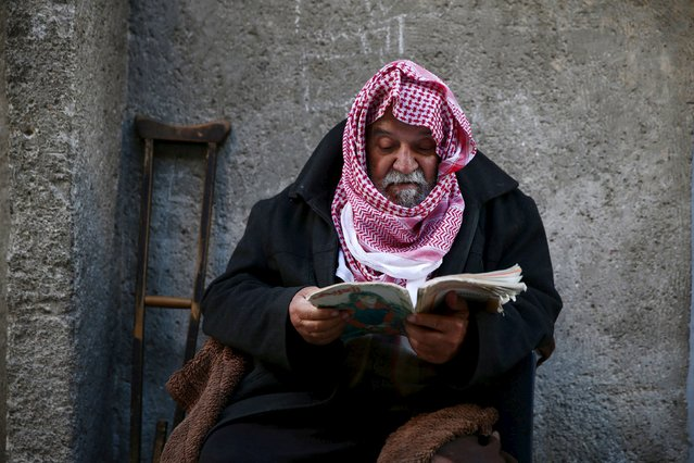 Abu Hatem, 75, reads as he sits outdoor in the rebel held Douma neighborhood of Damascus, Syria March 20, 2016. (Photo by Bassam Khabieh/Reuters)