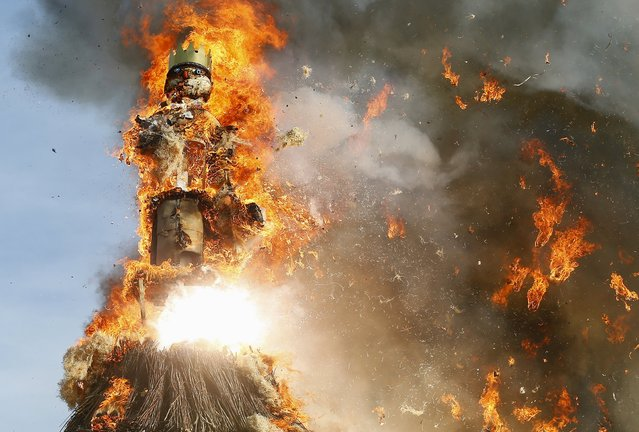 "The Boeoegg, a snowman made of wadding and filled with firecrackers, burns atop a bonfire in the Sechselaeuten square in Zurich April 13, 2015. As the bells of St. Peter's church chime six o'clock, the bonfire below the ""Boeoegg"" is set alight and mounted guildsmen gallop around the pyre to the tune of the Sechselaeuten March. (Photo by Arnd Wiegmann/Reuters)"