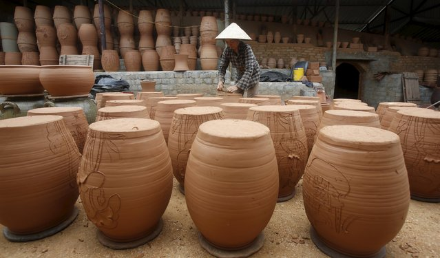 A woman works at a factory producing clay pots at Phu Lang pottery village in Bac Ninh province, Vietnam, May 14, 2015. The village is part of an old pottery triangle in northern Vietnam which includes Bat Trang and Tho Ha, and has been producing pottery since the 13th century, according to local media. (Photo by Reuters/Kham)