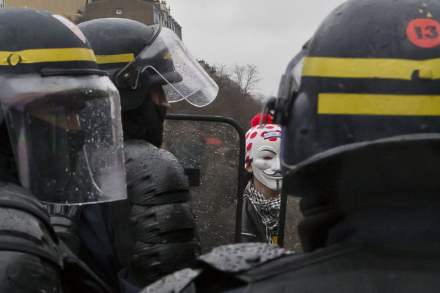 A masked student face-off French police officers during a rally to protest the new labor law in Paris, Thursday, March 31, 2016. Students and workers hold street protests across France while train drivers, teachers and others are on strike to reject a government reform relaxing the 35-hour workweek and other labor rules. (Photo by Michel Euler/AP Photo)
