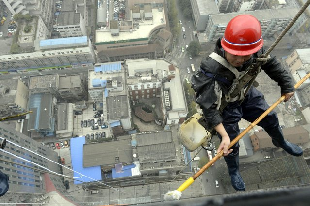 Spidermen (window cleaners) clean outer walls for a supermarket in Chengdu, capital of southwest Chinas Sichuan Province. (Photo by Caters News)