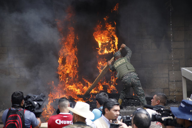 A soldier works to put out a tire fire started by protesters outside the main entrance into the U.S. Embassy during a protest against the government of President Juan Orlando Hernandez, in Tegucigalpa, Honduras, Friday, May 31, 2019. Protesters are demanding the government revoke decrees that they say would lead to massive, uncompensated layoffs of public employees and the privatization of state hospitals. (Photo by Elmer Martinez/AP Photo)