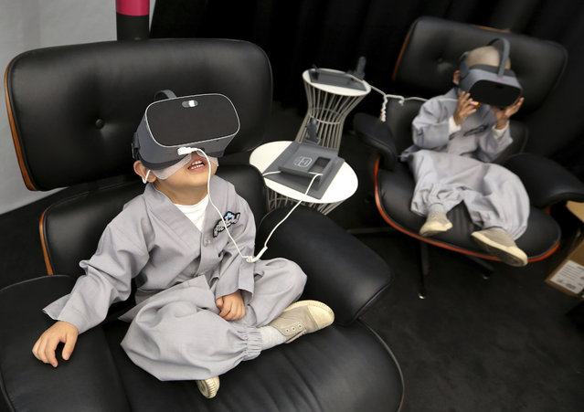 In this May 7, 2019, photo, shaven-headed young boys wear VR devices to experience 5G service at LG UPlus 5G experience place in Seoul, South Korea. Ten children entered a temple to have an experience of monks' life for three weeks to celebrate upcoming Buddha's birthday on May 12. (Photo by Ahn Young-joon/AP Photo)