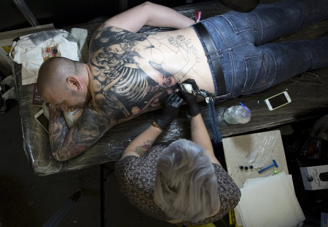 A man is tattooed during the Great British Tattoo Show in Alexandra Palace in north London, Britain May 23, 2015. (Photo by Neil Hall/Reuters)