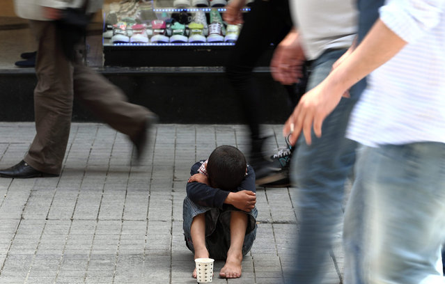 A Syrian boy begs on the Istiklal street on a warm day as people walk in Istanbul, Turkey, 19 May 2015. (Photo by Sedat Suna/EPA)