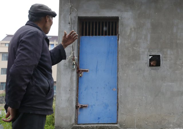 Ma Pinglin, 37, looks out as he speaks to his father through a hole on the wall of a locked house, serving as Ma's dwelling, in Houtang village, Zhejiang province, China, May 14, 2015. According to the family, Ma turned violent and often hit people and set fire in the house after he was diagnosed of mental dissociation in 2009. Ma's father had to build a small house, which cost about 20,000 yuan (3,222 USD), to lock him up, as the family cannot afford a full treatment. (Photo by William Hong/Reuters)