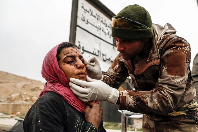 A woman injured in a mortar attack is treated by medics in a field clinic as Iraqi forces battle with Islamic State militants, in western Mosul, Iraq March 2, 2017. (Photo by Zohra Bensemra/Reuters)