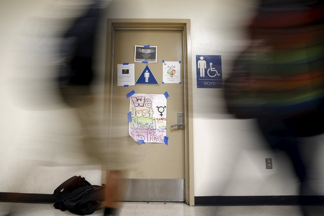 Students walk past a protest sign on a bathroom which helped lobby for the first gender-neutral restroom in the Los Angeles school district at Santee Education Complex high school in Los Angeles, California, U.S., April 18, 2016. (Photo by Lucy Nicholson/Reuters)