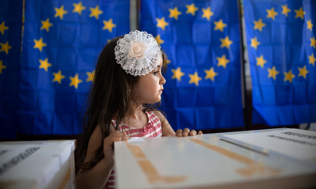 In this Sunday, May 26, 2019 picture a little girl waits for her mother to vote, backdropped by voting cabins with curtains depicting the European Union flag in Baleni, Romania. After voters turned out for last week's European Parliament elections in numbers not seen in 20 years, the leaders want to show they can respond quickly to people's concerns, aiming to name all four top jobs – the commission chief, a replacement for Donald Tusk as European Council president, a new foreign policy chief and head of the European Central Bank – at a summit June 21-22. (Photo by Andreea Alexandru/AP Photo)