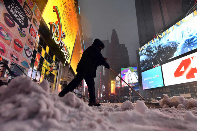 A man plows snow from a street at the Times Square in New York on March 14, 2017. (Photo by Jewel Samad/AFP Photo)