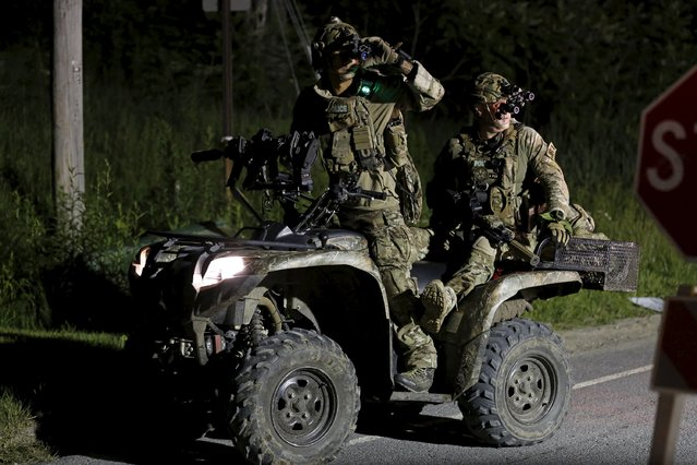Law enforcement agents ride an all-terrain vehicle during a search for escaped prisoners south of Malone, New York June 26, 2015. Law enforcement officers shot and killed a man who is believed to be one of two prisoners who broke out of a maximum security prison in New York three weeks ago and the second escapee is still at large near the Canadian border, police said on Friday. (Photo by Chris Wattie/Reuters)