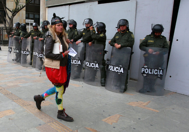 A demonstrator walks in front of riot policemen during May Day protests in Bogota, Colombia, May 1, 2016. (Photo by Jon Nazca/Reuters)