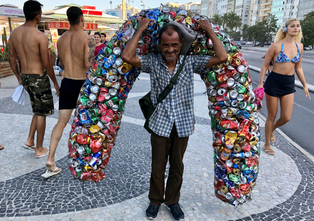 A man carries recycled cans at Copacabana beach in Rio de Janeiro, Brazil on July 24, 2019. (Photo by Jorge Silva/Reuters)