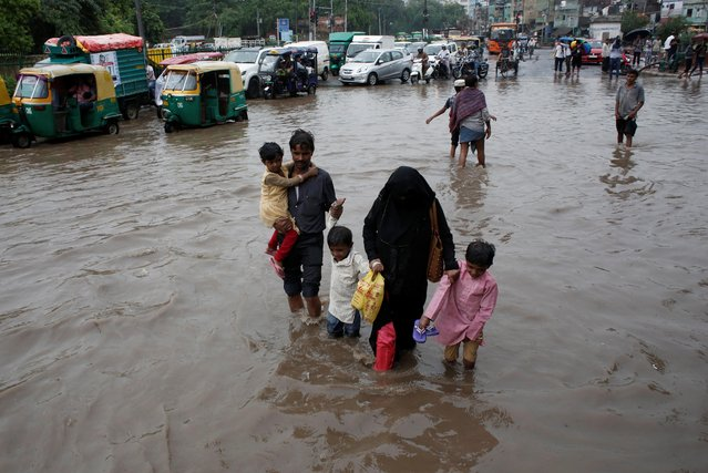 A family wades through a flooded street during heavy rains in New Delhi, India, August 6, 2019. (Photo by Adnan Abidi/Reuters)