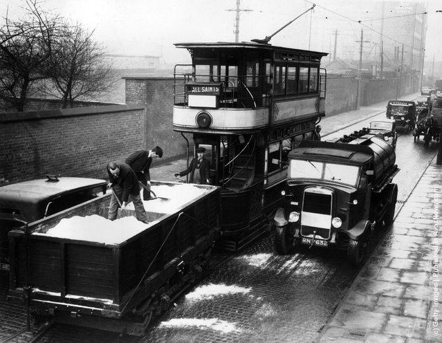 1936: Salt being spread on the street from a trailer fitted to a tram car in a test run in Manchester in case snow should fall