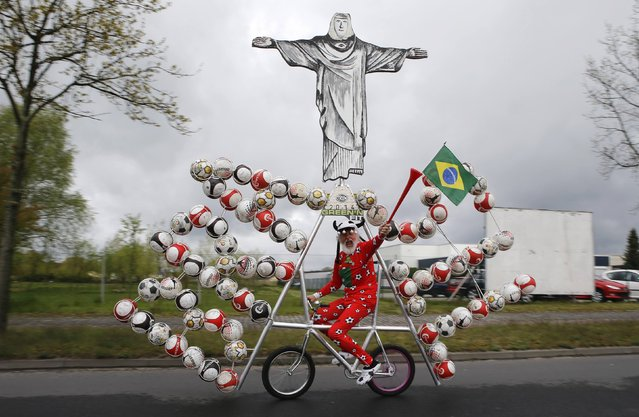 """German bicycle designer Didi Senft, also known as """"El Diablo"""", rides his new bicycle creation to commemorate the 2014 FIFA World Cup, in the town of Storkow, southeast of Berlin April 18, 2014. (Photo by Fabrizio Bensch/Reuters)"""
