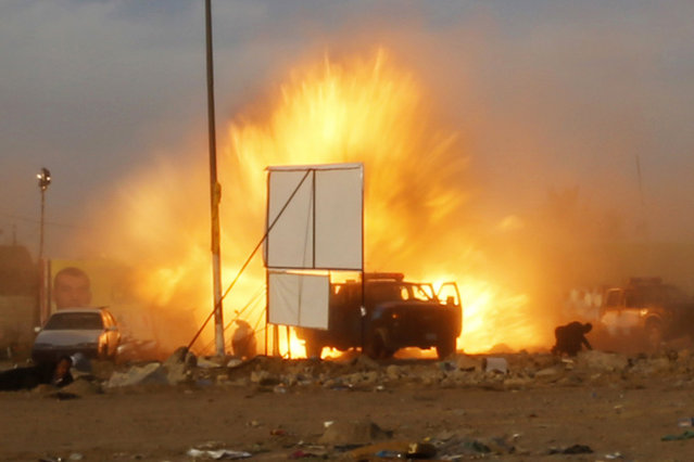 An explosion is seen during a car bomb attack at a Shi'ite political organisation's rally in Baghdad, April 25, 2014. A series of explosions killed 18 people at a Shi'ite political organisation's rally in Iraq on Friday, police and medical sources said. The militant group, Asaib Ahl Haq (League of the Righteous), introduced its candidates for elections on April 30 at the rally in eastern Baghdad. (Photo by Thaier al-Sudani/Reuters)