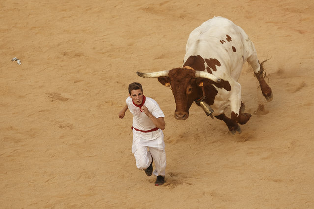 A reveler is chased by a bull during a celebration held at the bullring after the running of the bulls of the San Fermin festival in Pamplona, Spain, Tuesday, July 7, 2015. (Photo by aniel Ochoa de Olza/AP Photo)