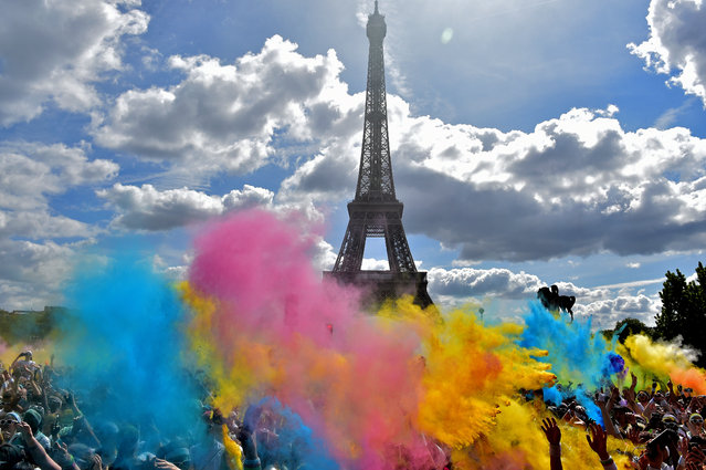 People take part in the Color Run 2017 's edition in front of the Eiffel Tower in Paris, on April 16, 2017. The Color Run is a five kilometres paint race without winners nor prizes, while runners are showered with colored powder at stations along the run. (Photo by Christophe Archambault/AFP Photo)