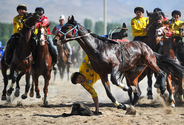 Teams Chuy (in yellow) and Osh Region players struggle in the final buzkashi match as part of the 2019 World Nomad Games, 22km away from the town of Talas, at the foot of the Karool-Choku Mountain in Kyrgyzstan on September 21, 2019. (Photo by Abylai Saralayev/TASS)