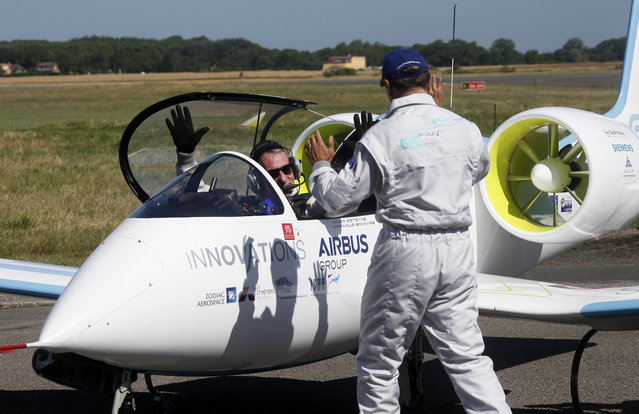 Pilot Didier Esteyne, left, raises his arms after crossing the Channel with his European planemaker Airbus E-Fan prototyp, at the Calais Airport, Friday, July 10, 2015. Airbus flew its electric plane across the English Channel for the first time Friday, hours after a French pilot made a similar voyage in his electric plane – journeys seen as a symbolically important step toward making electronic flight viable in the long term. (Photo by Michel Spingler/AP Photo)