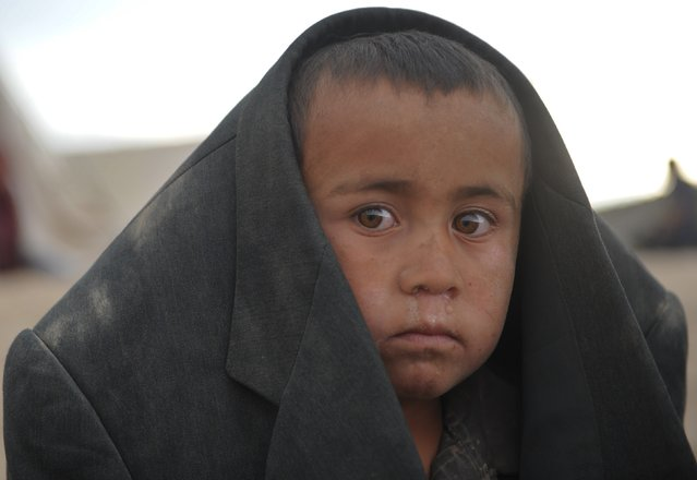 An Afghan boy looks on he stands at the site of a landslide at the Argo district in Badakhshan on May 3, 2014. Landslides buried a village in northern Afghanistan on Friday, killing at least 350 people and leaving thousands of others feared dead, as rescuers searched desperately for survivors trapped under the mud. Villagers at the disaster site in Badakhshan province used shovels to dig through rocks and dirt, with national authorities, the United Nations and the US-led military force all racing to assess the damage and provide help. (Photo by Farshad Usyan/AFP Photo)