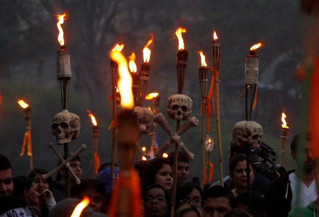 Demonstrators hold torches with skulls, inscribed with the acronym of the Honduran Institute of Social Security (IHSS), during a march to demand the resignation of Honduras' President Juan Orlando Hernandez in Tegucigalpa, July 10, 2015. (Photo by Jorge Cabrera/Reuters)