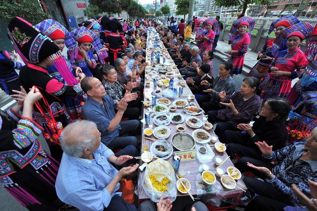 Villagers clap as they gather to have a meal together along a street to celebrate an ethnic Zhuang festival in Baise, Guangxi Zhuang Autonomous Region, China, April 25, 2016. (Photo by Reuters/Stringer)