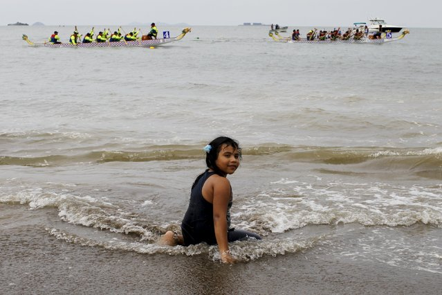 A girl sits on the beach as participants compete during the Chinese dragon boat festival in the outskirts of Panama City, July 12, 2015. (Photo by Carlos Jasso/Reuters)