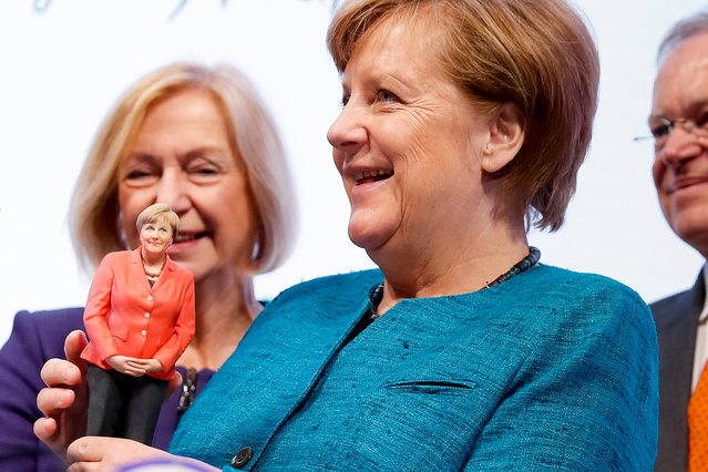 German Chancellor Angela Merkel (C) holds a sculpture according to her image from a 3D printer at the Siemens stand during the opening round trip at the Hannover Messe 2017 industrial trade fair in Hanover, northern Germany, 24 April 2017. Poland is the guest-country this year. The Hannover Messe (Hanover Fair) is the world's biggest industrial fair. The exhibition runs from 24 to 28 April 2017. (Photo by Carsten Koall/EPA)