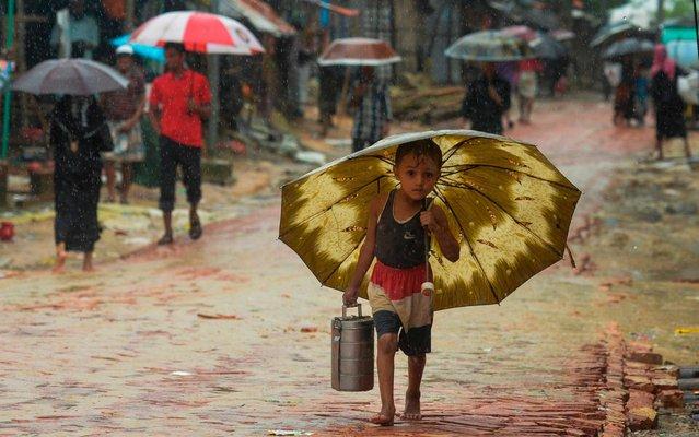A Rohingya refugee boy shelters under an umbrella as he makes his way during a monsoon rainfall at Kutupalong refugee camp in Ukhia on Setember 12, 2019. (Photo by Munir Uz Zaman/AFP Photo)