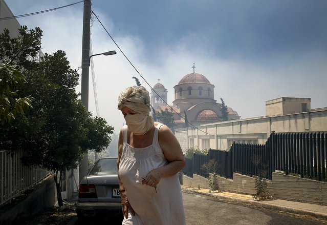 An elderly woman covers her nose and mouth as she walks away from a forest fire close to Saint George church in an Athens neighborhood, July 17, 2015. (Photo by Yannis Behrakis/Reuters)