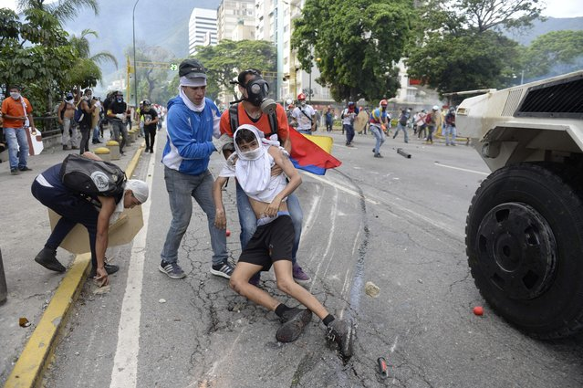An opposition demonstrator ran over by a National Guard control vehicle is dragged away by a fellow demonstrator during a protest against Venezuelan President Nicolas Maduro, in Caracas on May 3, 2017. (Photo by Federico Parra/AFP Photo)